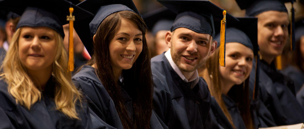 Male and female graduates in cap and gown sitting, posing for the camera