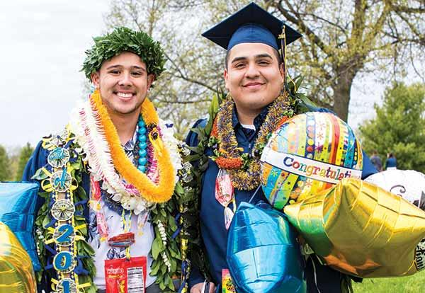 Two male graduates clothed in their regalia surrounded by balloons and leis