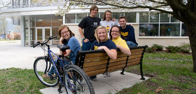 a small group of male and female students pose on a bench with a bicycle next to them